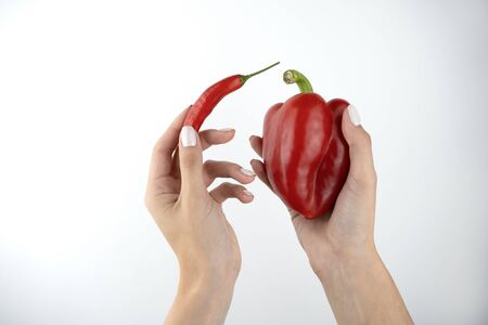 image of woman's hands holding red fresh chilly pepper and sweet red pepper on isolated white background.