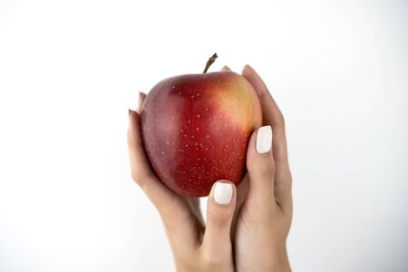 image of woman's hands holding fresh red apple in both hands on isolated white background.