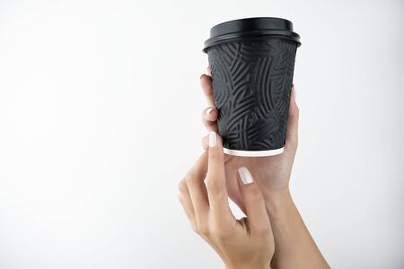 woman's hands holding papper cup with coffee tea cacao on isolated while background, take away concept. 免版税图像