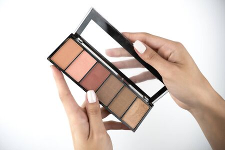 woman's hands holding blush contouring palette isolated white background.