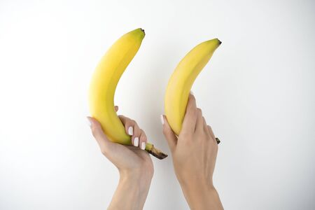 image of woman's hands holding fresh bananas on isolated white background. 免版税图像