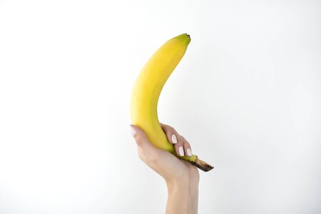 image of woman's hand holding fresh banana on isolated white background.