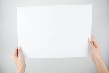 woman's hands holding banner sign with white blank empty paper billboard with copy space for text over gray background. 免版税图像