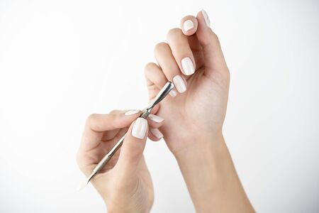 picture of hands using cuticle pusher while doing manicure on isolated while background .