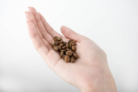 Woman's hand holding medium roasted coffee beans on isolated white background.