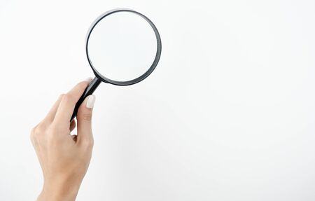 image of spying woman's hand holding magnifying glass on isolated white background.