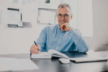 handsome gray-haired smiling man sits in his office while working on business project looks happy, takes notes to his agenda, work routine concept 免版税图像