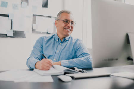 handsome gray-haired smiling man sits in his office while working on business project , checking his laptop while taking notes to his agenda, work routine concept