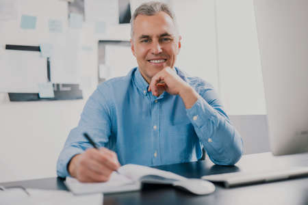 handsome gray-haired man sits in his office writing notes to his agenda while working on business project looks satisfied, work routine concept 免版税图像