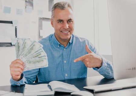 handsome gray-haired man sits in office holding cash in his hand like card deck looking excited while working on business project , money making motivation concept