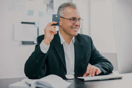 handsome gray-haired businessman in elegant suit sits in office holding bank card in hand looking excited while working on business project , money making motivation concept 免版税图像