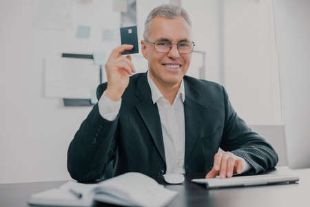 handsome smiling gray-haired businessman in elegant suit sits in office showing bank card looking excited while working on business project , money making motivation concept