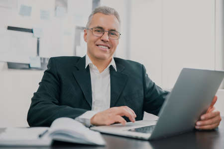 handsome gray-haired businessman in elegant suit sits in office looking excited while working in lap top on new business project , money making motivation concept 免版税图像
