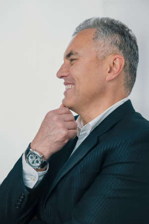 half-face portrait of handsome smiling gray-haired businessman in elegant suit standing half a turn on isolated white background, holds hand with watch near face 免版税图像