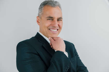 portrait of handsome smiling gray-haired businessman in elegant suit stands half a turn on isolated white background, holds hand near face, work routine concept