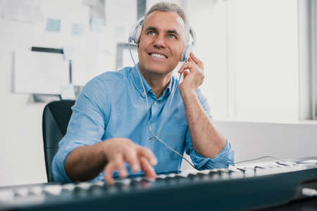 handsome gray-haired smiling man sits in his music studio playing keyboard piano wearing earphones looking excited and happy, music record concep, art 免版税图像
