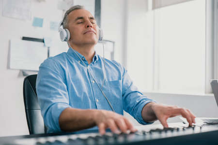 handsome gray-haired smiling man with headphones sits in music studio playing keyboard piano enjoying music looking excited and happy, music record concep, art of composition 免版税图像