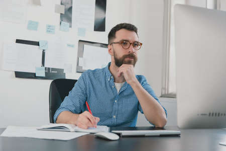 young bearded man sits in office holding hand near face while working on business project looks busy, takes notes to his agenda, work routine concept