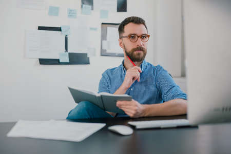 young bearded man sits in office holding pen near face while working on business project looks satisfied, takes notes to his agenda, work routine concept