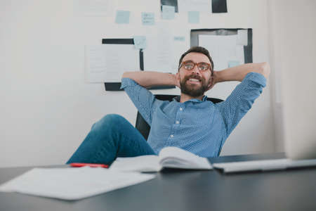 handsome bearded smiling man sits in his office having break while working on business project looks happy, with his hands behind head, work routine concept