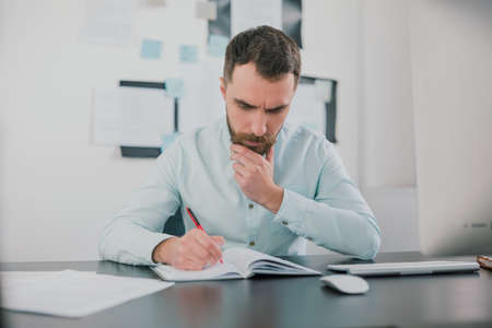 young bearded brunette man looking busy while working on business project in his modern office, takes notes to his agenda, work routine concept