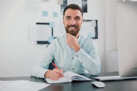 young bearded brunette smiling man looking happy while working on business project in his modern office, takes notes to his agenda, work routine concept