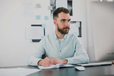 young bearded brunette man sits in his office looking happy while working on business project looks satisfied, takes notes to his agenda, work routine concept