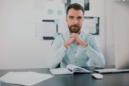 young bearded brunette man looking serious while working on business project in his modern office, holds hands near his face, work routine concept 免版税图像