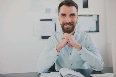 young bearded brunette smiling man looking happy while working on business project in his modern office, holds hands near his face, work routine concept