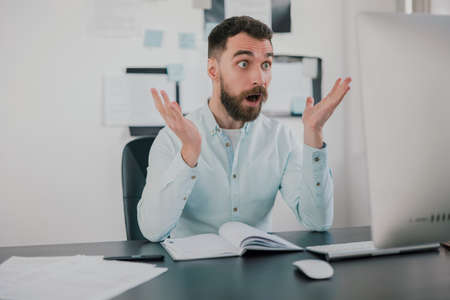 young bearded brunette man looking surprised while working on business project in his modern office, holds hands in the air, work routine concept
