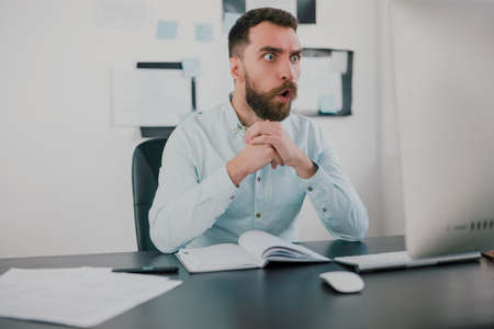 young bearded amazed brunette man looking surprised while working on business project in his modern office, holds hands together , work routine concept
