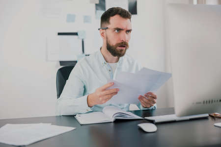 young bearded brunette man looking amazed while working on business project in his modern office, holding documents in his hand, work routine concept