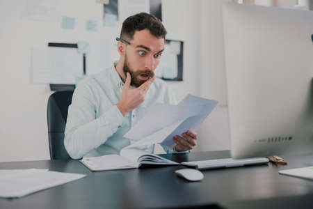 young bearded brunette man looking amazed while working on business project in his modern office, studying documents in his hand, work routine concept