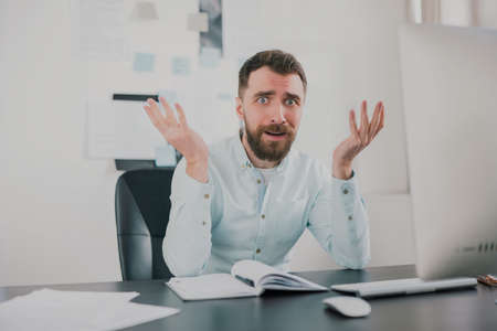 young bearded brunette man looking desperate while working on business project in his modern office, holding his hands in the air, work routine concept 免版税图像