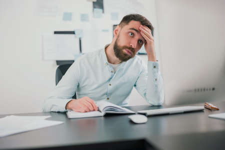 young bearded brunette man looking tired and exhausted while working on business project in his modern office, holding his hand near forehead, work routine concept 免版税图像