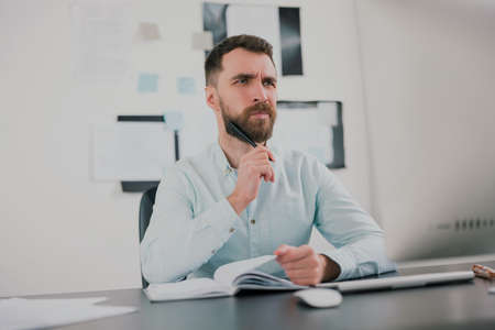 young bearded brunette man looking thoughtful while working on business project in his modern office, holding pen in his hand, work routine concept