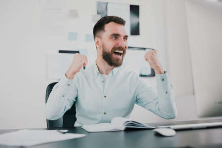 young bearded brunette man looking happy after successful business contract, sitting in his modern office with hands in winning position, success and well-being concept 免版税图像