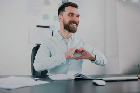 young bearded brunette man looking happy after successful business contract, sitting in his modern office with hand showing heart, success and well-being concept