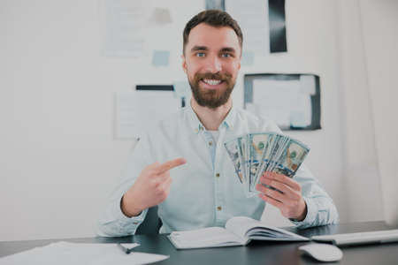 bearded man sitting in modern office holding cash in his hand like card deck looking excited while working on business project , money making motivation concept