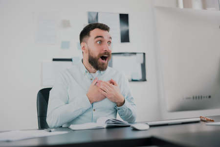 young bearded brunette man looking happy after successful business contract, sitting in his modern office with hands near heart, success and well-being concept