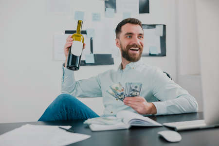 bearded man drinking wine celebrating successful business deal in modern office holding cash in his hand like card deck looking excited, money making motivation concept