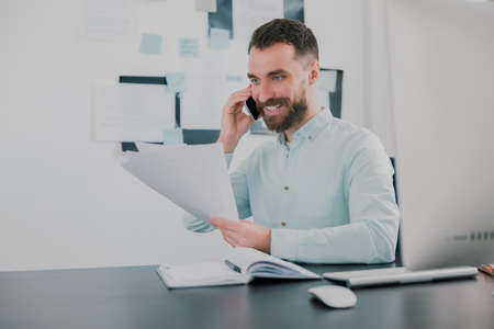young bearded smiling man working on business project in his modern office, holding documents in his hand, having phone conversation, work routine concept