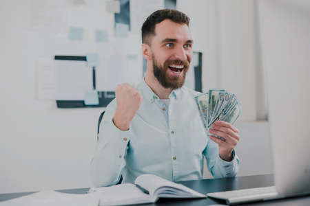bearded man sitting in modern office holding cash in his hand like card deck looking excited while working in his office, money making motivation concept