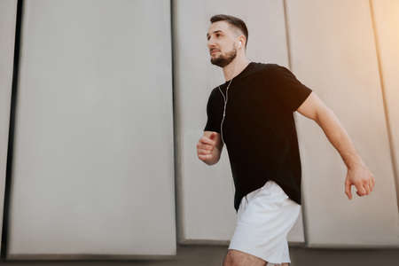 young handsome brunette man in sportswear jogging on the street listens his favorite music, healthy fit lifestyle Standard-Bild