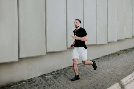young handsome strong brunette man in sportswear jogging on the street listens his favorite music, healthy fit lifestyle