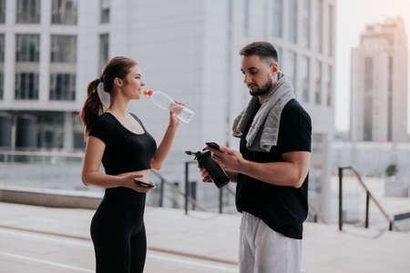young couple handsome brunette man checks his smartphone and beautiful woman in sportswear drinks water having rest during street workout, , healthy fit lifestyle Standard-Bild