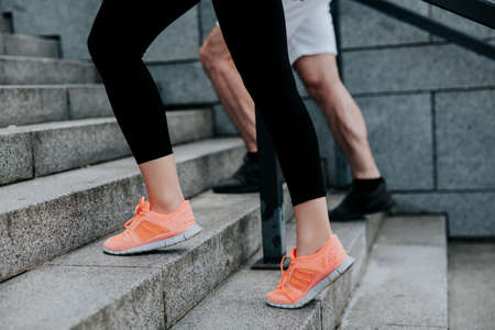 mans and womans feet in sportshoes doing workout on the street, climbing up the stairs, healthy fit lifestyle