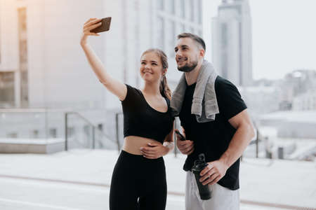 young couple handsome brunette man and beautiful woman in sportswear doing selfie on smartphone during street workout, healthy fit lifestyle