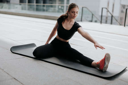 happy young handsome brunette woman in sportswear warming up before street workout stretching on yoga mat, healthy fit lifestyle Standard-Bild