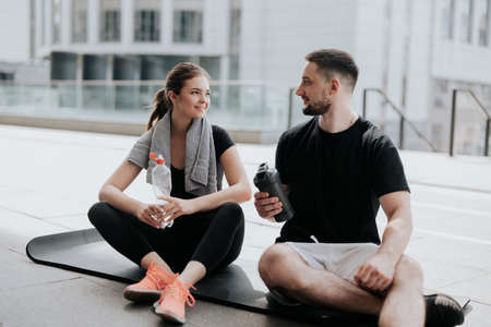 happy young couple brunette beautiful woman and handsome man in sportswear having rest on yoga mat, drinking water after hard street workout healthy fit lifestyle